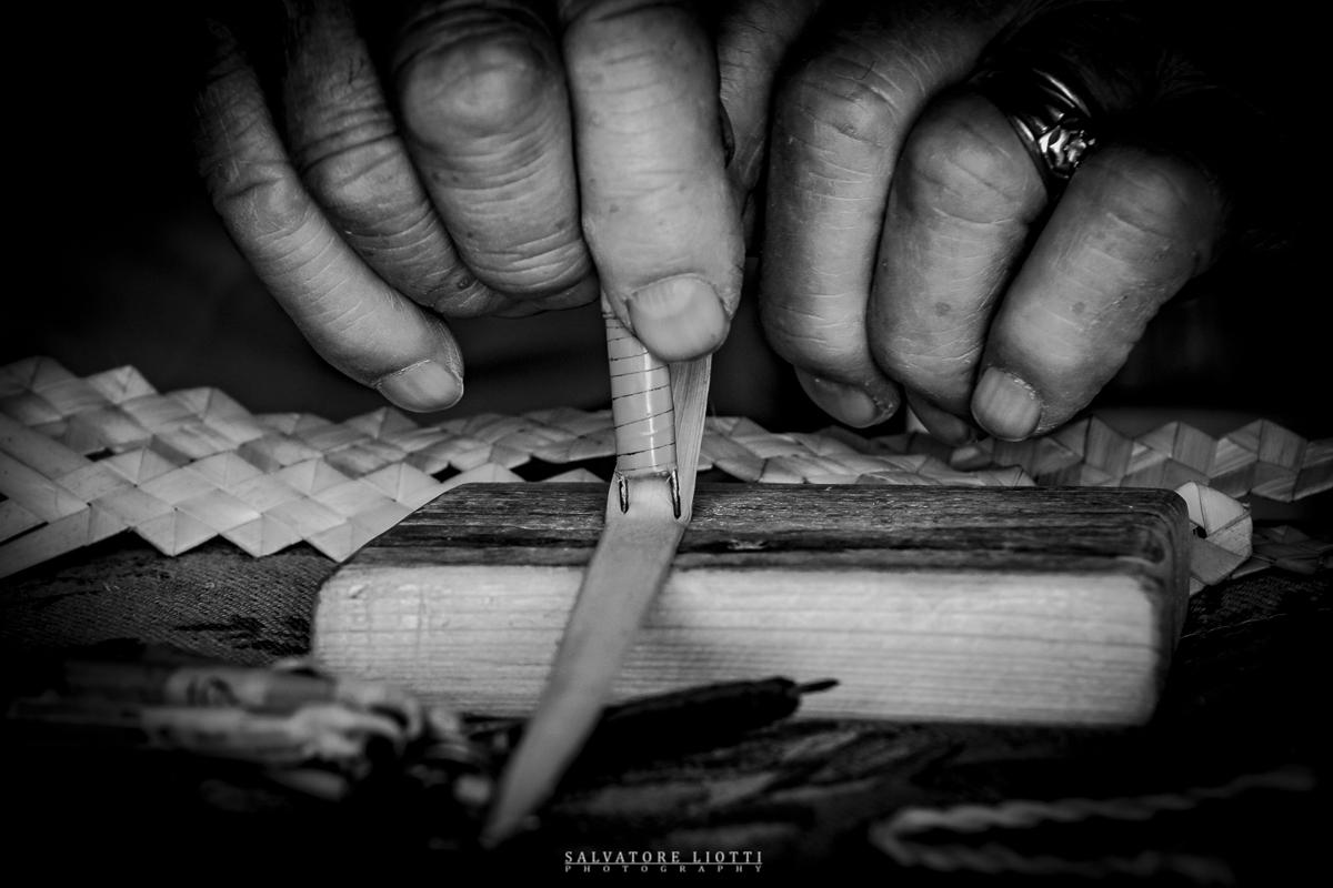 mani anziane che tagliano steli di paglia