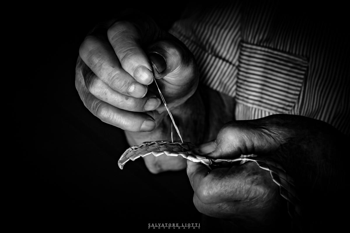 treccia di paglia viene cucita da mani vecchie