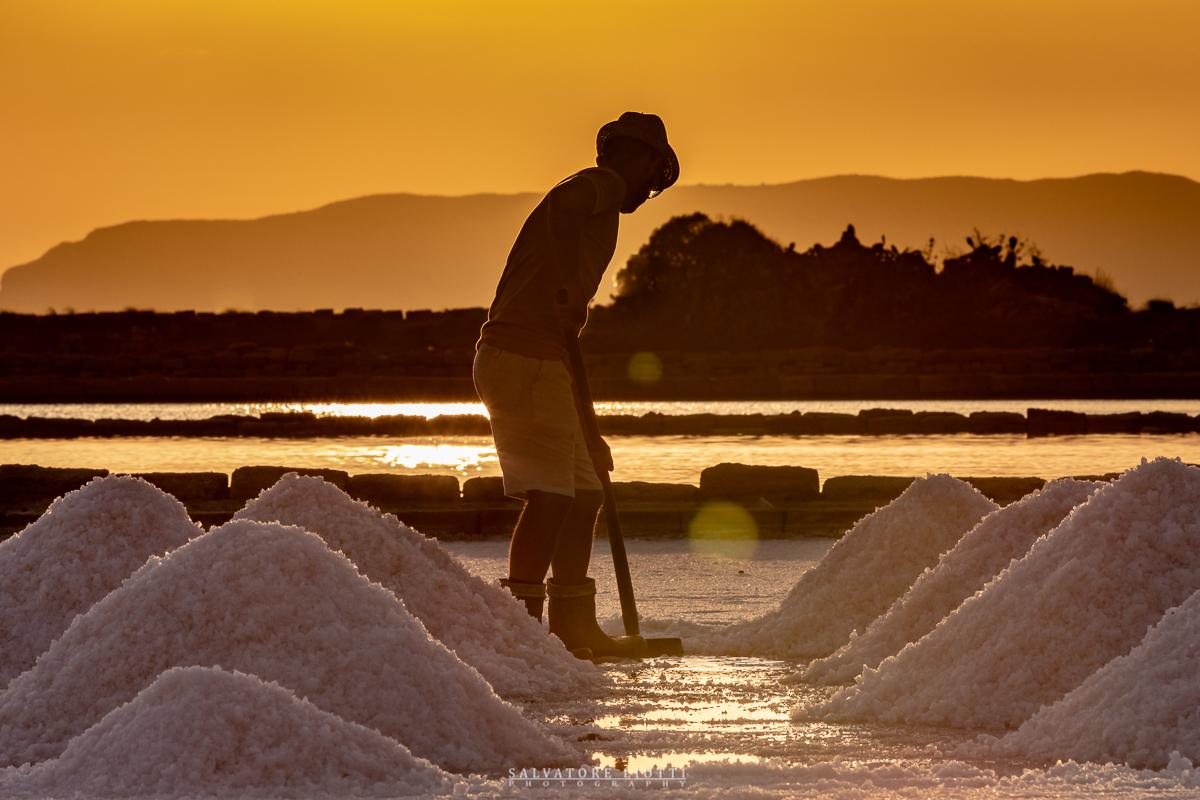 persona intenta a raccogliere il sale