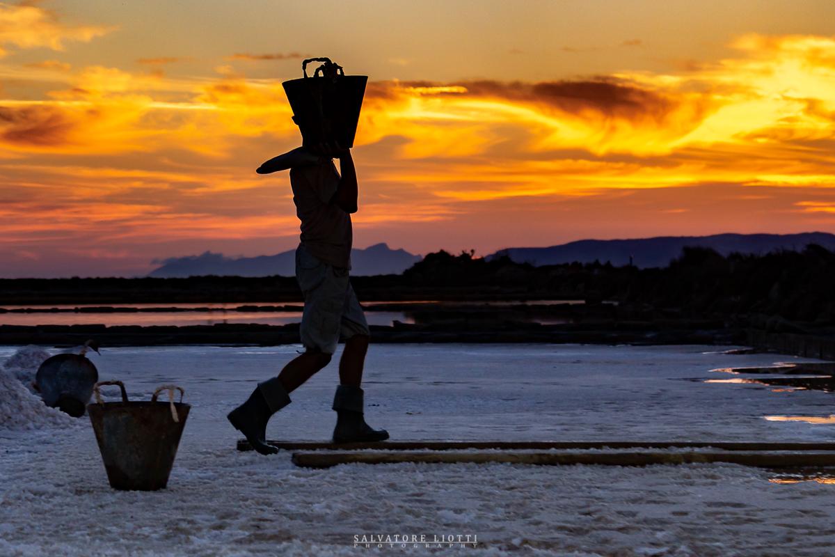 persona al tramonto trasporta secchio pieno di sale