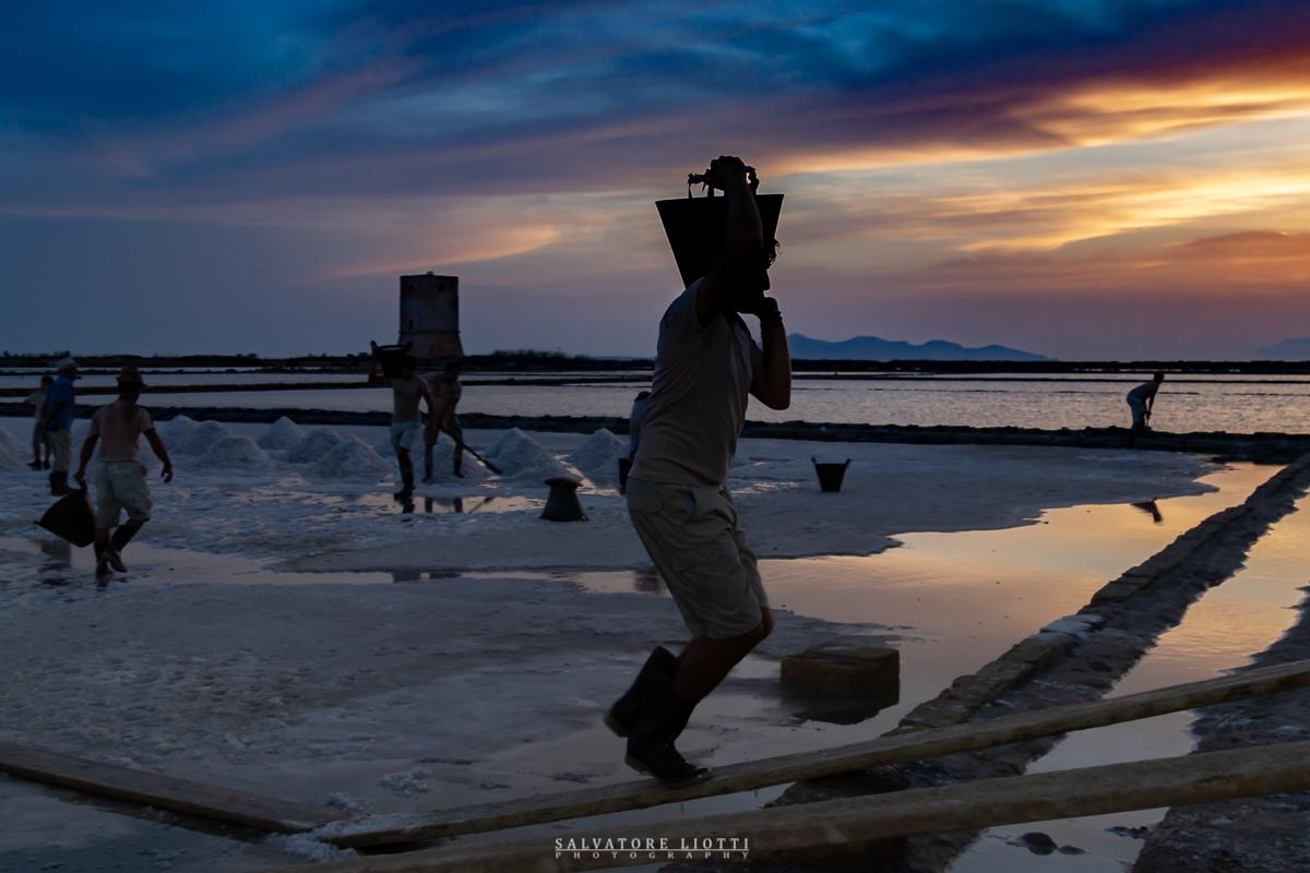 persone al tramonto raccolgono il sale