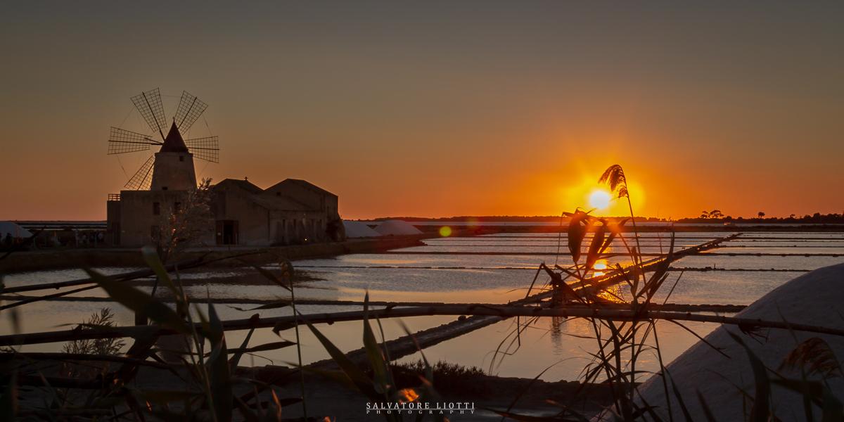 tramonto con mulino a vento e saline