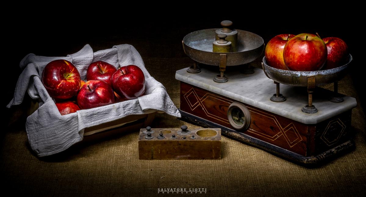 composizione bilancia antica e mele tecnica light painting