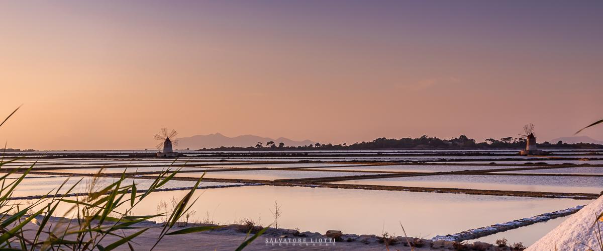 tramonto siciliano con saline e mulini a vento